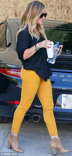 The 25-year-od showed off her sculpted physique donning mustard skinny jeans, a fitted button-up and her signature tan ankle boots
