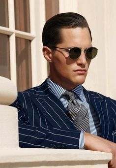 Round sunglasses and slicked back hair.