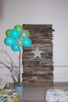 Wall made from weathered pallets. Balloon and branches in bucket with up lighting.