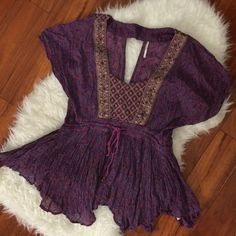 Free people top Gorgeous Free People top. Stunning purple with amazing details. Flows top, has a tie in the middle to adjust for an empire waist look. Size M runs a little big. Used a handful of times but still in great condition. Free People Tops