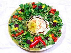 Μια Χριστουγεννιάτικη σαλάτα σε μια στρογγυλή πιατέλα, με βάση σπανάκι [ή άλλο πράσινο λαχανικό], χωρισμένα ανά διαστήματα με σπαράγγια, σκορπισμένα ντοματίνια, φέτες πατζαριών και κίτρινη πιπεριά, κομμένα με κουπ πατ σε αστεράκια κ.λ.π.