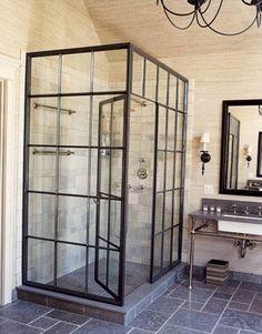 glass shower doors and grey tiled floors. bathroom designed by Jeffrey Bilhuber