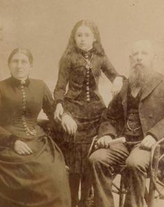 13.) In this photograph, the girl standing in the middle is the deceased. The photographer attempted to make her look more alive by drawing on her pupils.