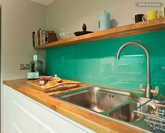 Backsplash, Splashback, Glass, Colour, Turquoise, blue green, Glass splash backs have gone the way of the dinosaur, but something about the colour here and natural look of the timber and floating shelf let this one pass...kind of a retro vibe going on.
