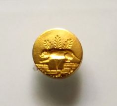Rare gold seal (distinctive example of seal carvers' workshops) depicting a barking guard dog sitting on a garden enclosure. Poros (Seaport of Knossos), Neopalatial period. Archaeological Museum of Heraklion.
