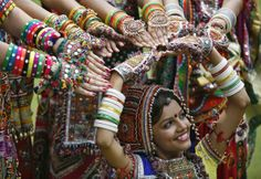 """A girl dressed in traditional attire poses as she takes part in rehearsals for the """"garba"""" dance ahead of Navratri festival in the western Indian city of Ahmedabad September 29, 2013. Navratri, held in honour of Hindu Goddess Durga, is celebrated over a period of nine days where thousands of youths dance the night away in traditional costumes. Navratri starts on October 5. (Photo by Amit Dave/Reuters)"""