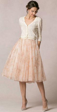 Falda media altura con vuelo de color pastel, rebeca beis y tacones beis.