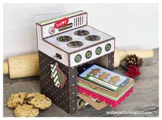 An oven gift box with a door that opens to reveal a gingerbread cookie box, and a drawer that pulls out at the bottom. A perfect way to give some baked treats and gift cards for Christmas! SVG Cuts and Echo Park Paper.