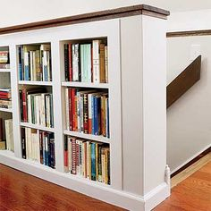 Built-in bookshelf on half-wall along stairs