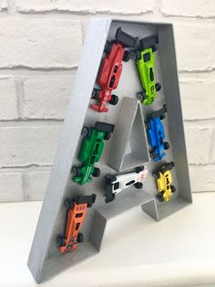 A large wooden letter filled with a selection of colourful toy cars. This would look striking in a boys room or a nursery and make a lovely birthday gift for a little or big boy in your life! Also a perfect choice for Fathers Day!  The letter stands at 22cm/8.7 tall and 3cm/1 wide. Choose a few letters and spell your name or a word!  The colour of cars is random and if you would like a different colour letter other than silver please let me know - red, blue, green, white, purple, pi...