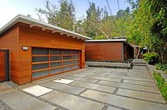A mid-century driveway with large pavers and gravel between the stones leads into a wood and glass sectional garage door. This look won't work for every home, but it is a distinctive style.