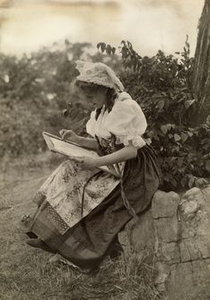 Picture Id: 938068  A Bohemian girl works on embroidery while seated on a stone wall. Location: Bohemia.  Photographer: R. D. SZALATNAY/ National Geographic Stock