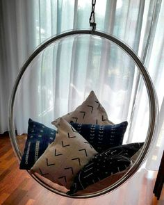 African mudcloth pillows relaxing in iconic Bubble Chair by  Eero Aarnio