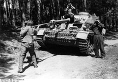 """Crew member cleaning the barrel of his early Panzer IV Ausf. H (11. Pz.-Div) during operation """"Zitadelle""""."""