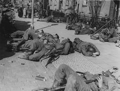 American soldiers resting on the sidewalk of a German city in 1945