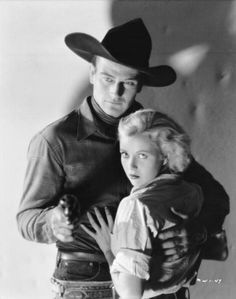 Promo still for Riders of Destiny, 1933, with Cecilia Parker. Duke is 'Singin' Sandy', the screen's second singing cowboy after Ken Maynard in his early talkies.