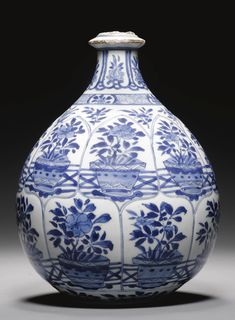 A CHINESE BLUE AND WHITE HUQQA BASE MADE FOR THE PERSIAN MARKET, KANGXI,  1662-1722    pyriform with bulbous base with tapering shoulders terminating in a ringed mouth, the body moulded and decorated in underglaze cobalt blue with imbricated lobed registers enclosing potted flowering plants, the neck with an arcade of flowers and diamond trellis motif, base with floral bouquet  23cm. height