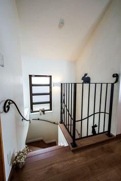 うさぎの階段アイアンと、くるりとした手すりアイアンが白い壁に映え、美しい。