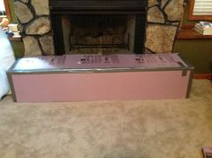 Pink foam board from Home Depot, cut to fit around fireplace. I duck taped it together (underneath as well). Then, I covered it with quilt batting (folded to form layers). Lastly, I got some cheap fabric from hobby lobby and hot glued it underneath.