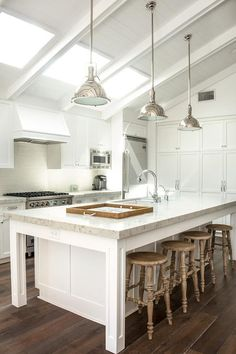 Three Restoration Hardware Harmon Pendants illuminate a white kitchen island with four legs topped with carrera marble fitted with a sink and gooseneck faucet lined with rustic backless counter stools.