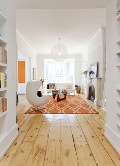 Unstained wooden floor boards not only add to the brightness of the room, but they also showcase the natural patterns and texture of the wood. Source