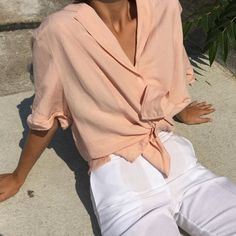High-waisted white pants and light pink blouse for minimal look