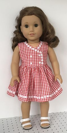 A sweet summer dress for your doll. This dress is made from a red and white gingham fabric. The bodice is fully lined and has four white buttons sewn to the front. The skirt is fully gathered. White daisy trim is sewn to the top bodice edge and the hem. Dress closes in back with