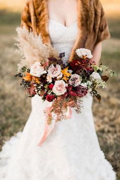 Fall wedding inspiration for a mountainside bride. Floral design by Wild Fleurette, Virginia wedding and event florist, destination wedding florist, Alisandra Photography, bridal portrait, winter wedding, colorful bouquet, bouquet of pampas grass, roses, leaves, berries in blush, mauve, yellow and burgundy red, bride, wedding style, bridal gown, strapless dress, bouquet, silk ribbon, outdoor wedding, classic bride, autumn bouquet, bold bouquet, pink, blush, rose #fallwedding