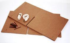 Cadeira Xis. de papelão.  Duas placas com mesmo tamanho e recorte que se encaixam. O travamento é feito com cinto e sticks de madeira.