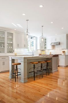 Classic kitchen with industrial accents.  Grey painted kitchen island, white subway tile with dark grout, light hardwood floors.
