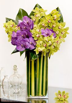 "Great Orchid Mix  This a mesmerizing arrangement is designed with Blooms of Pistachio Green Cymbidium Orchids, Vanda Orchids and Philodendron Plant Leaves all arranged in a 18"" x 8"" glass vase lined with Flax Leaves. This arrangement is approx. 36""-38"" tall."