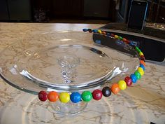 """M Cake Display:  Attach M candies to the edge of a cake pedestal with melted chocolate """"glue""""."""