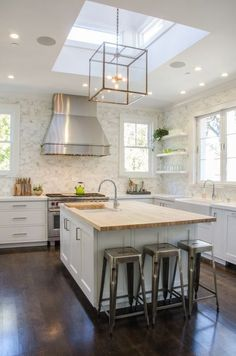 Stainless Range Hoods - Design Chic - fun light fixture and great stainless stools in the kitchen