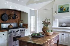 A silver ice bucket corrals wooden spoons beneath iron and copper pots in this rustic, Spanish-inspired family kitchen.