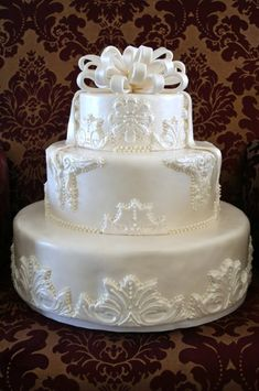 Fondant covered three-tiered cake with appliques and fondant bow