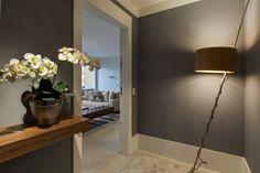O hall do elevador também merece cuidados. Esse recebeu pintura cinza, aparador de madeira e uma luminária marcante. Projeto Asenne Arquitetura via Casos de Casa.