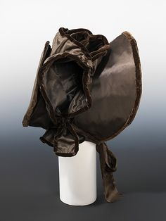 Velvet-trimmed silk bonnet, British, ca. 1820. Bonnets worn during this period were elaborately decorated and varied widely in shape and type of decoration. This particular hat has a great deal of presence because of the sheer size and boldness of the shape. The undulating ruffles created by the velvet-edged satin adds another dimension to its presence. The wearer's face would be flirtatiously framed by the deep arc of the brim.