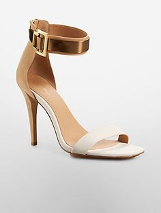 a metallic ankle strap buckle accent with a back zip closure.