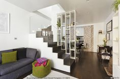 Open-plan interior with tall shelves as partition and view of dark brown staircase with glass balustrade; grey couch and green beanbag in foreground