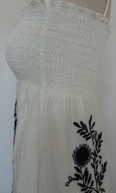 Juicy Couture Maxi Hippie Dress Black Embroidery. Festival Dress, Juicy Couture Original, designer dresses One of Juicy Couture's most coveted pieces designed with a hippie inspiration and masterful embroidery. Feminine crushed creamy silk cascades over an underneath skirt slip. Delicate smocked and finely stitched top with stretch for a perfect, stay-put fit. Straight neckline with tasseled self-tie adjustable straps. Exquisite floral and vine embroidery in black down skirt, front and back