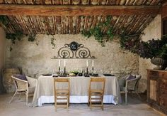 A rustic french country dining room: whitewashed plaster walls, beamed ceilings, in the heart of Provence