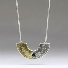Half circle pendant in silver and gold cast in beach sand and set with a sapphire - Aztec inspired contemporary pendant Half Circle, Delft, Contemporary Jewellery, Gold Pendant, Aztec, Sapphire, It Cast, Gold Necklace, Jewelry Making