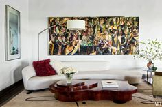 In the living room of Tara and Peter Guber's Los Angeles home by Nancy Heller, a Jessica Rice triptych overlooks a Vladimir Kagan sofa from Ralph Pucci International and a Jean de Merry cocktail table.