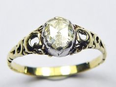The center diamond is then accented by 4 old rose cut diamonds which are also sitting in the uniquely designed, silver loop-like patterns on either side of the center diamond. This handmade ring is a must see! Antique Gold Rings, Diamond Solitaire Rings, Rose Cut Diamond, Silver Roses, English, Fancy, Engagement Rings, Antiques, Handmade