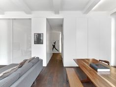 The living room is at the center of the apartment with the bedroom concealed behind the frosted sliding glass doors and the home office behind the flush doors. The corridor at the center leads to the front door, kitchen and bathroom.