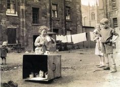 Children playing outside tenements in Glasgow I used to do this pretend shopkeeper..lol