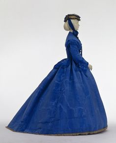 Day dress, England, ca. 1867. Heavy, iridescent silk moiré, satin, and taffeta, with fringe, in vivid blue from new synthetic dyes. Skirt shape exhibits the transition from round hoop skirts to bustles. On display at the Fashion Museum in Ludwigsburg Castle, near Stuttgart.