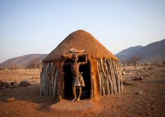 Himba Boy In The Entrance Of His Hut, Okapale, Namibia (by Eric Lafforgue)