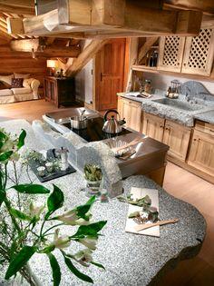 Luxueuse cuisine en bois métal et pierre. Plan de travail en marbre taillé. Intérieur chalet original et haut de gamme.