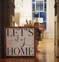 """Let's Stay Home"" Approximately 24"" x 24"" Printed Board + Stained Wood Frame Please note these boards are lightweight (2-5 pounds) making decorating and rearranging a breeze! Hangers are included with"